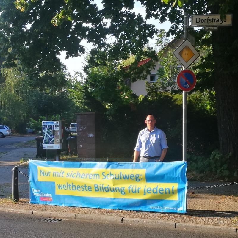 """Marcel Otto, Mitglied im Vorstand der FDP Lichtenberg, hinter dem Banner mit der Aufschrift """"Nur mit sicherem Schulweg: weltbeste Bildung für jeden!"""""""